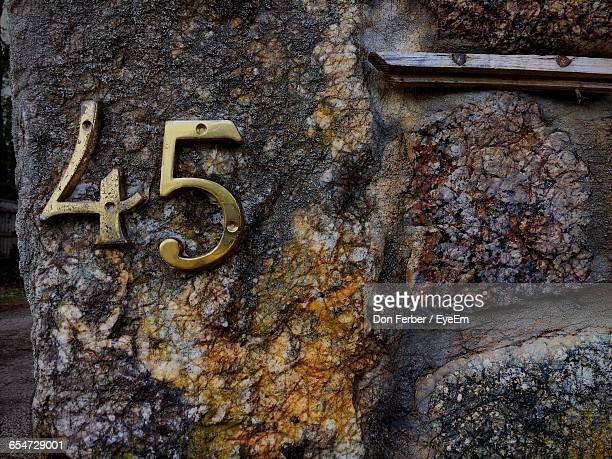 Close-Up Of Metallic House Number On Rock