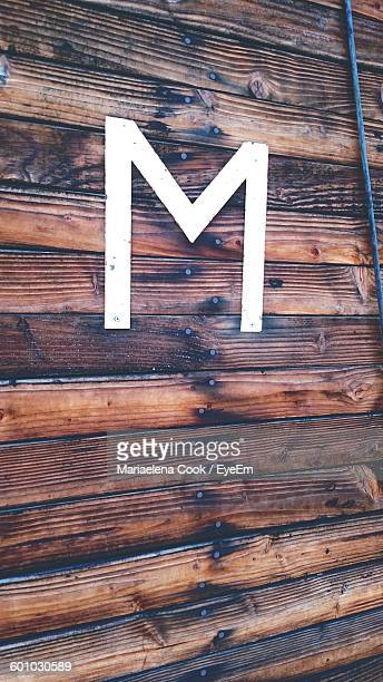 Close-Up Of Metallic Letter M On Wooden Wall