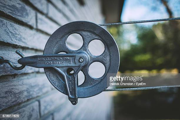 Close-Up Of Metallic Pulley On Hook Over House