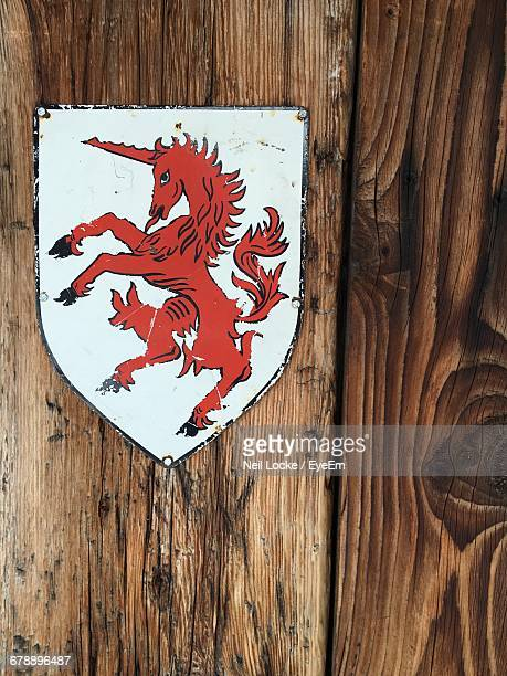 Close-Up Of Metallic Red Unicorn Badge On Wooden Wall