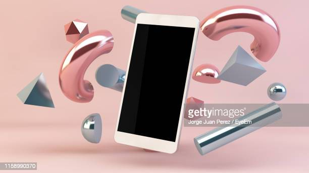 close-up of metallic shapes and smart phone against pink background - in de lucht zwevend stockfoto's en -beelden