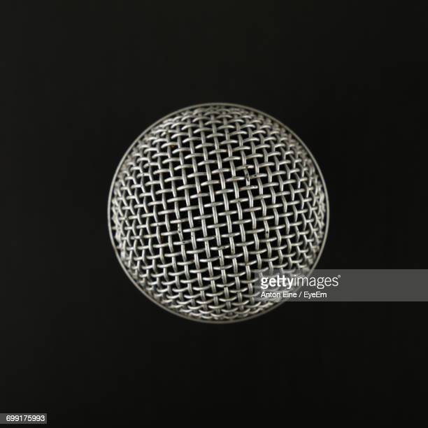 close-up of microphone against black background - microphone stock photos and pictures