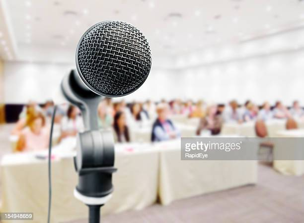 Closeup of microphone against blurry auditorum
