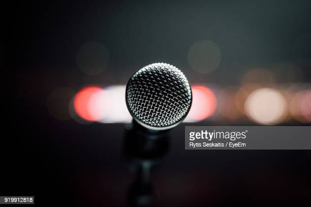 Close-Up Of Microphone Against Defocused Lights At Night