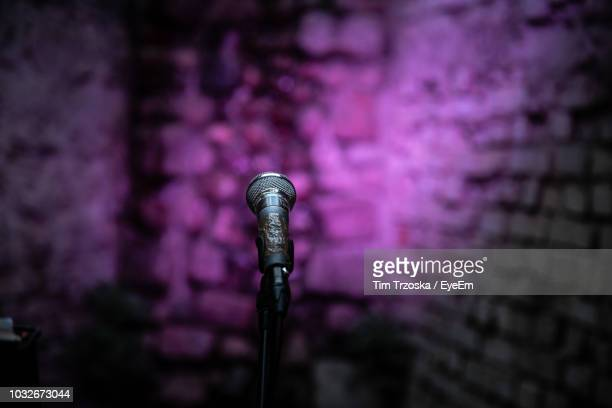 close-up of microphone against illuminated purple wall - microphone stand stock photos and pictures
