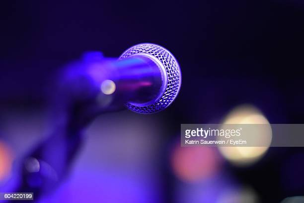 Close-Up Of Microphone Against Illuminated Stage Lights