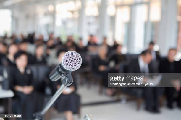 Close-Up Of Microphone Against People Sitting In Church