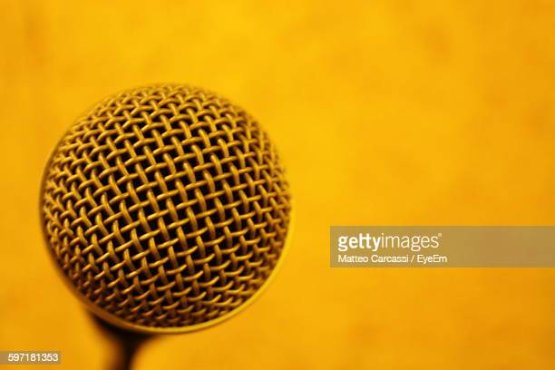 Close-Up Of Microphone Against Yellow Background