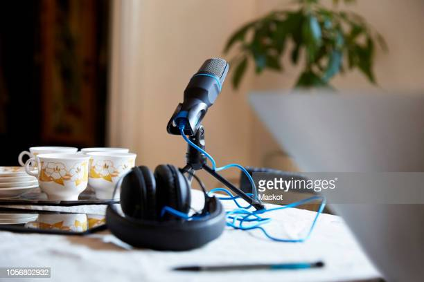 close-up of microphone and headphones with crockery on table at home - podcast stock-fotos und bilder