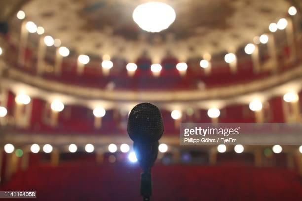 close-up of microphone at illuminated auditorium - theatervoorstelling stockfoto's en -beelden