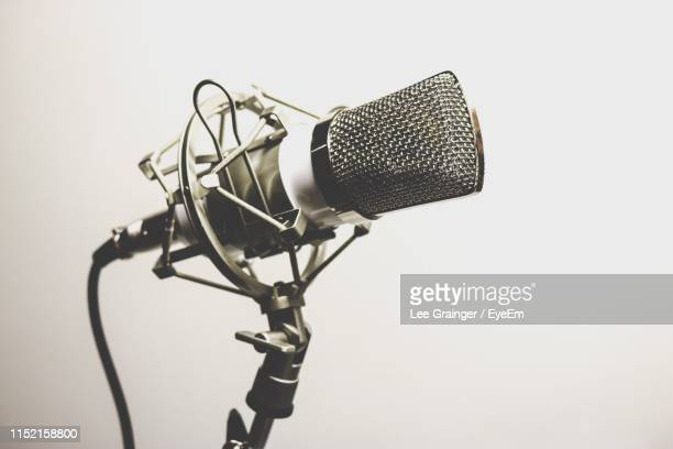 close-up of microphone on stand against white background - メディア機材 ストックフォトと画像