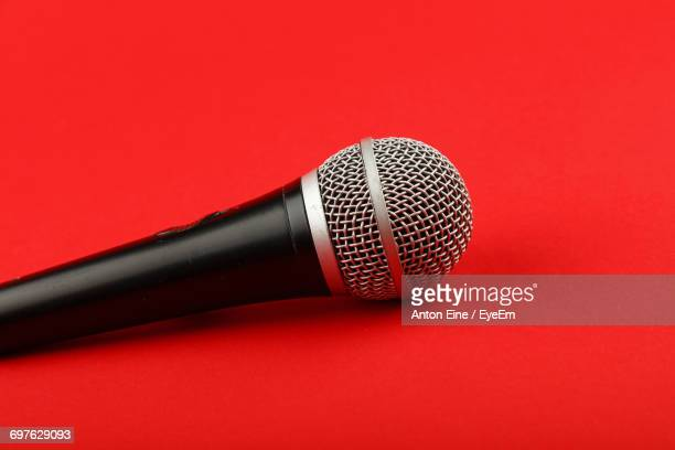 Close-Up Of Microphone Over Red Background