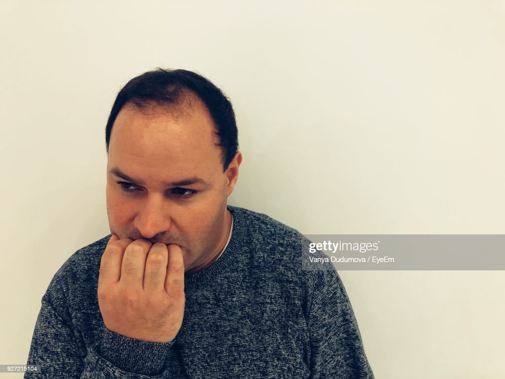 Closeup Of Mid Adult Man Biting Nails Over White Background Stock ...
