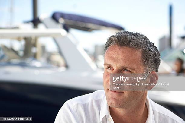 "close-up of mid adult man in front of yacht - ""compassionate eye"" ストックフォトと画像"