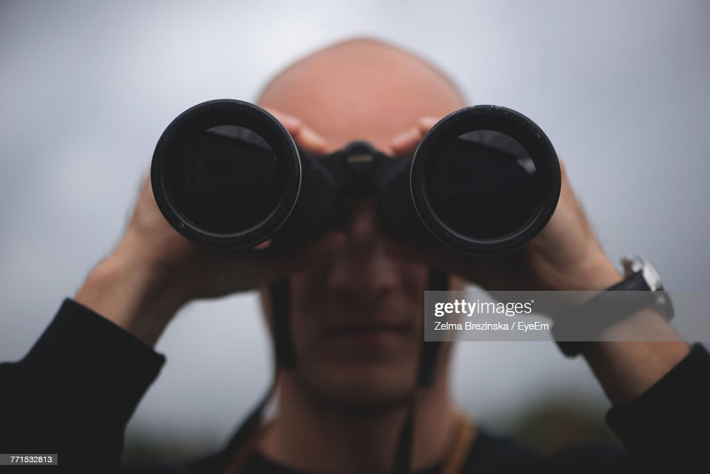 Close-Up Of Mid Adult Man Looking Through Binoculars While Standing Against Sky : Stock Photo