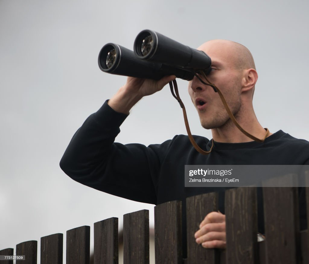 Close-Up Of Mid Adult Man Looking Through Binoculars While Standing Against Sky : Photo