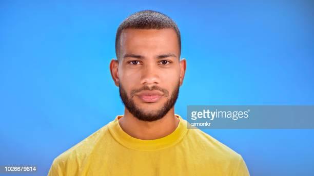 close-up do homem adulto médio - fundo azul - fotografias e filmes do acervo