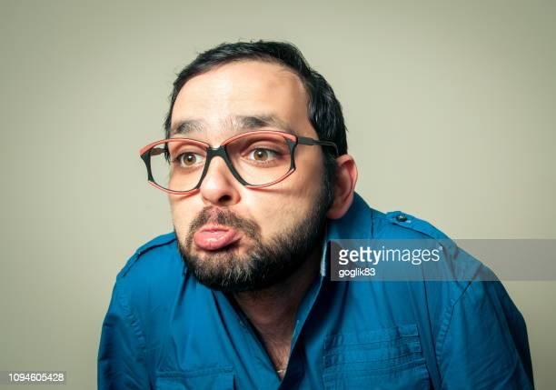 close-up of mid adult man pouting lips while shrugging against gray background - encogerse de hombros fotografías e imágenes de stock
