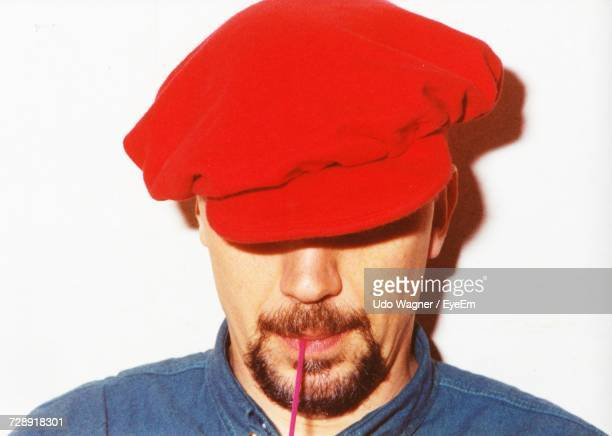 Close-Up Of Mid Adult Man Wearing Red Beret Against White Background