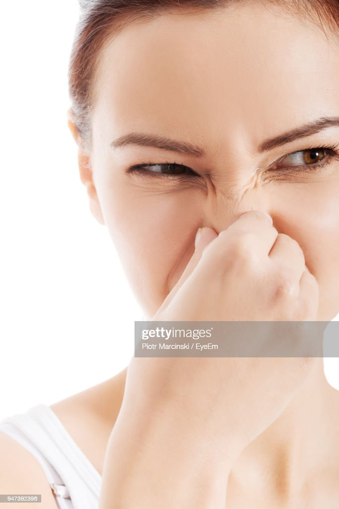Close-Up Of Mid Adult Woman Holding Nose Against White Background : Stock Photo