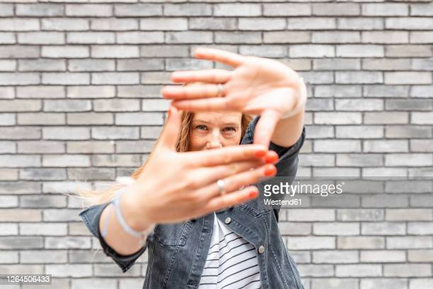 close-up of mid adult woman making finger frame against gray brick wall - human hand stock pictures, royalty-free photos & images