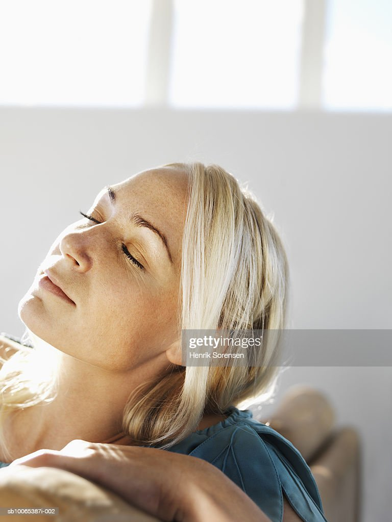 Close-up of mid adult woman sitting on sofa, eyes closed : Foto stock