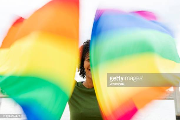 close-up of mid adult woman waving rainbow flags while standing in city - social justice concept stock pictures, royalty-free photos & images