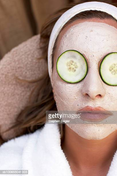 Close-up of mid adult woman wearing clay facial mask and cucumber slices on her eyes