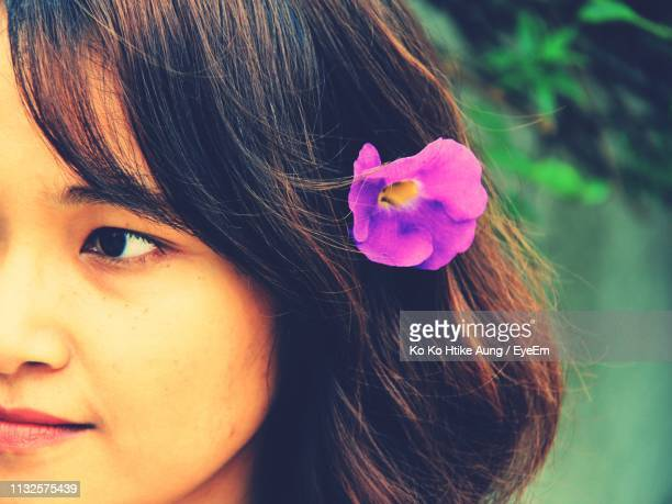 close-up of mid adult woman wearing pink flower in hair - ko ko htike aung stock pictures, royalty-free photos & images
