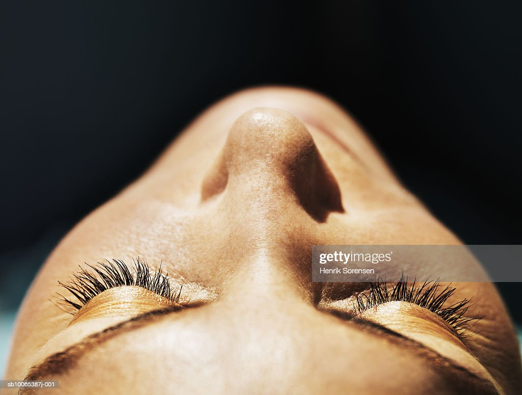 Close-up of mid adult woman's face, eyes closed, differential focus : Foto stock