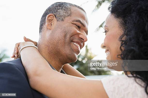 Close-up of middle-aged couple embracing and smiling
