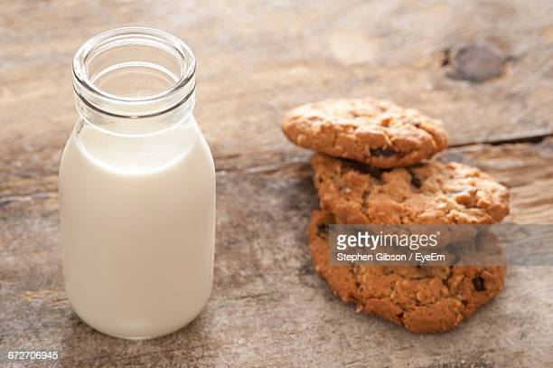 close-up of milk bottle and cookies on table - milk bottle stock pictures, royalty-free photos & images