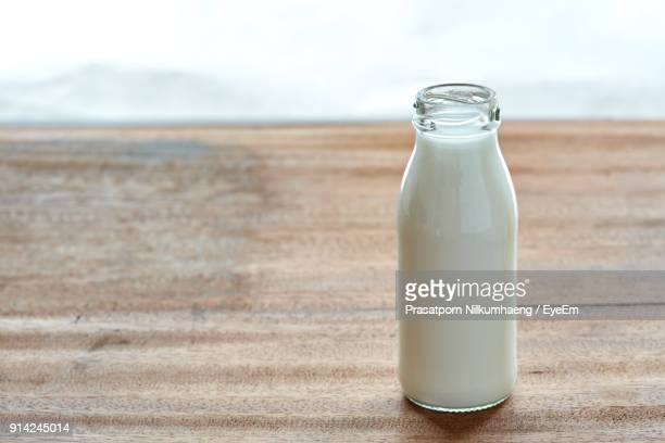 close-up of milk bottle on table against sky - milk bottle stock pictures, royalty-free photos & images