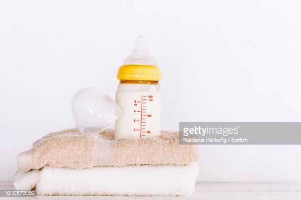 close-up of milk bottle on towels against white background - milk bottle stock pictures, royalty-free photos & images