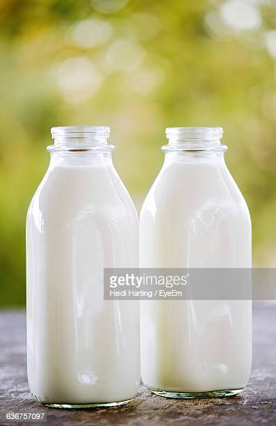 close-up of milk bottles on table - milk bottle stock pictures, royalty-free photos & images