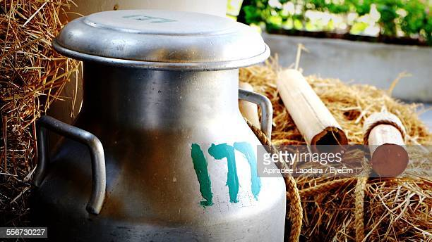 Close-Up Of Milk Churn Against Hay In Farm
