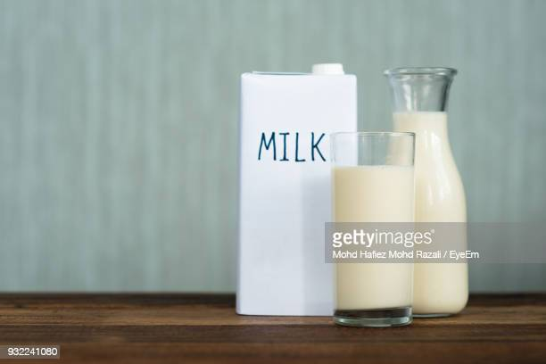 Close-Up Of Milk Glass And Jug With Text On Table