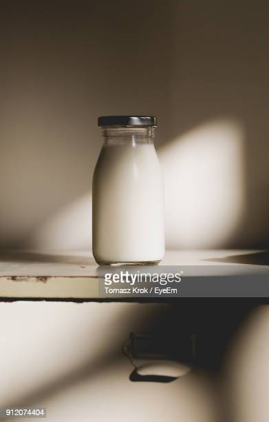 close-up of milk in bottle on table - milk bottle stock pictures, royalty-free photos & images