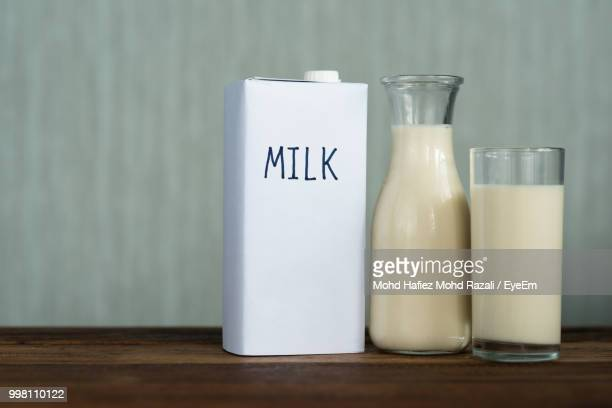 close-up of milk on wooden table against wall - carton stock pictures, royalty-free photos & images