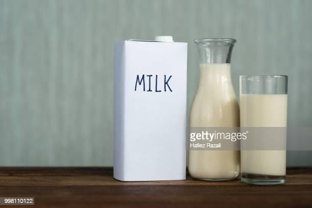 close-up of milk on wooden table against wall - milk carton - fotografias e filmes do acervo