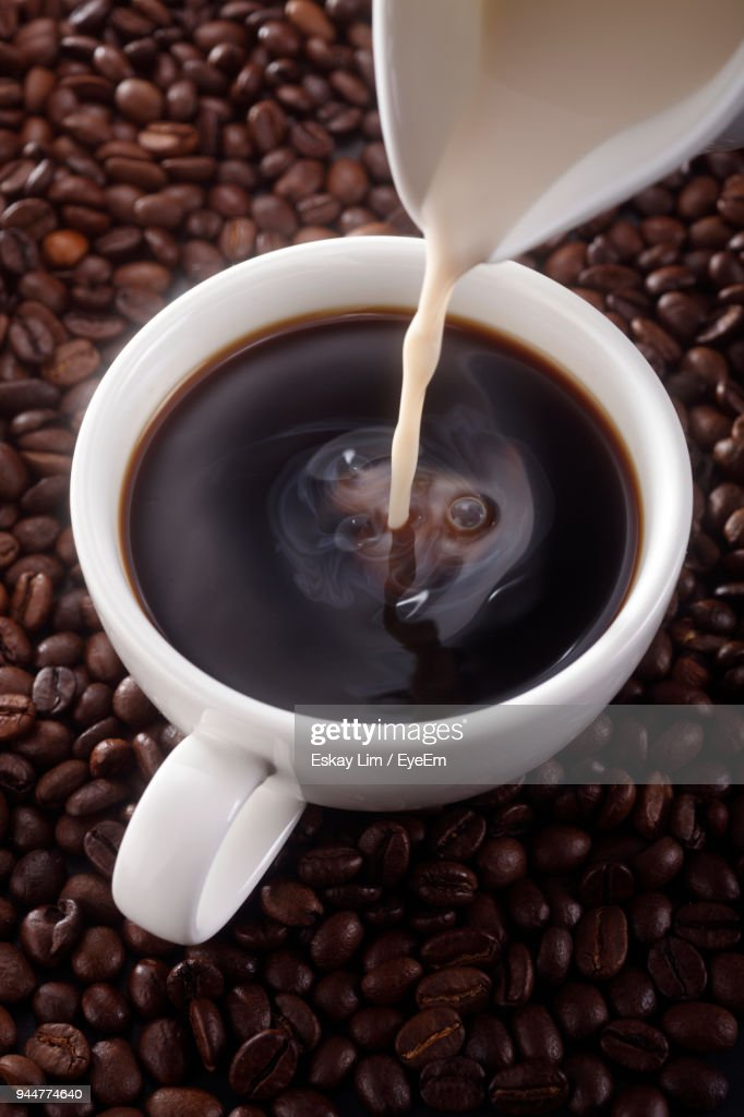 Close-Up Of Milk Pouring From Pot In Coffee Cup Amidst Beans : Stock Photo