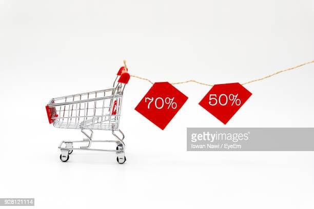 close-up of miniature shopping cart with placards over white background - percentage sign stock pictures, royalty-free photos & images