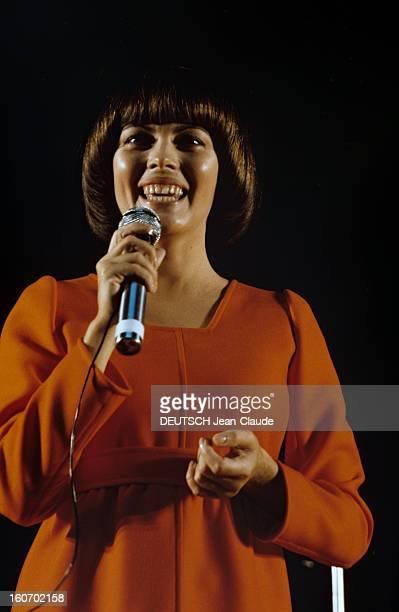 Closeup Of Mireille Mathieu In Gdr RDA 1972 Mireille MATHIEU vêtue d'une longue robe orange à manches longues chante sur scène micro en main droite...