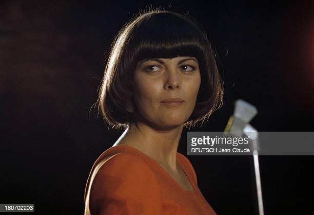 Closeup Of Mireille Mathieu In Gdr RDA 1972 Mireille MATHIEU vêtue d'une longue robe orange à manches longues chante sur scène visage tourné de côté...