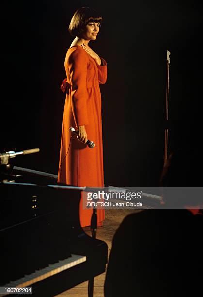Closeup Of Mireille Mathieu In Gdr RDA 1972 Mireille MATHIEU vêtue d'une longue robe orange à manches longues se teint debout sur scène micro en main...
