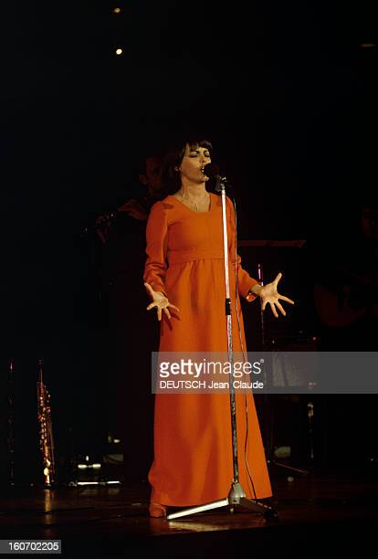 Closeup Of Mireille Mathieu In Gdr RDA 1972 Mireille MATHIEU vêtue d'une longue robe orange à manches longues chante debout mains ouvertes face à un...