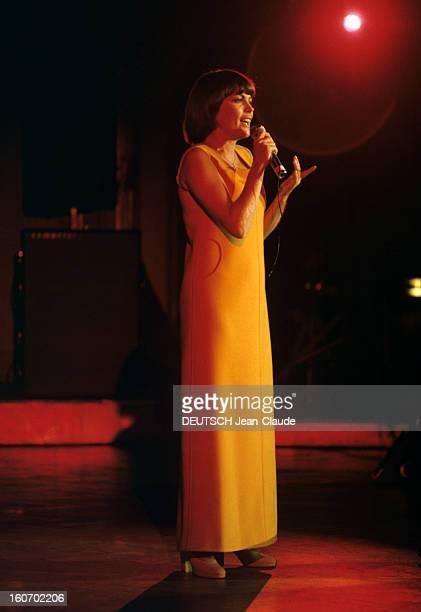 Closeup Of Mireille Mathieu In Gdr RDA 1972 Mireille MATHIEU vêtue d'une longue robe orange à manches longues chante debout sur scène micro en main...
