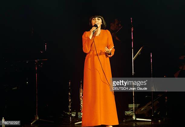 Closeup Of Mireille Mathieu In Gdr RDA 1972 Mireille MATHIEU vêtue d'une longue robe orange à manches longues chante debout sur scène micro en main à...