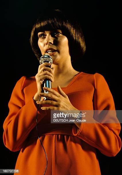 Closeup Of Mireille Mathieu In Gdr RDA 1972 Mireille MATHIEU vêtue d'une longue robe orange à manches longues chante sur scène micro en main droite à...
