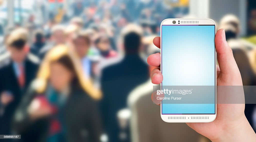 Closeup of mobile phone against crowd background : Stock Photo